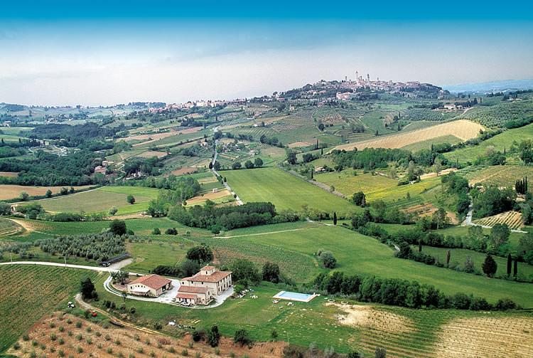 vista area de la casa rural con panormica sobre san gimignano siena